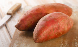 Raw sweet potatoes on wooden background . Selective focus Royalty Free Stock Photo