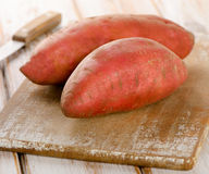 Raw sweet potatoes on a wooden background . Selective focus Royalty Free Stock Photos