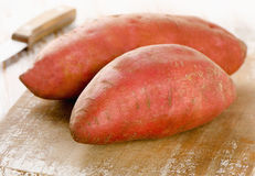 Raw sweet potatoes on a wooden background . Selective focus Royalty Free Stock Photo
