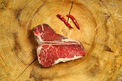 Raw T-Bone. T-Bone, Raw on a cutting board with dried chilli Stock Photo