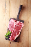 Raw t-bone or porterhouse steak. With a sprig of fresh rosemary on a vintage wooden board , overhead view on wood with copyspace Royalty Free Stock Images