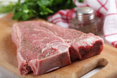 Raw T-bone steak. With pepper on the wooden cutting board Royalty Free Stock Photo