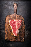 Raw T-bone steak on aged wooden cutting board on dark rust metal background, top view Stock Photos