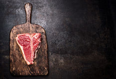 Raw T-bone steak on aged wooden cutting board on dark rust metal background, top view Stock Photography