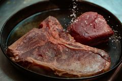 Raw T bone steak of beef meat in a frying pan against dark background. Selective focus. royalty free stock photography