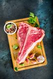 Raw t-bone steak. Raw fresh meat, t-bone beef steak with spices and herbs on cutting board, concrete table top view copy space royalty free stock photo