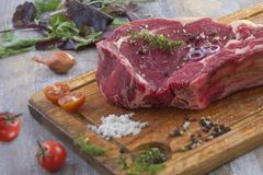 Raw T-bone Steak for grill or BBQ on cutting board over on a aged wooden background, top view Stock Photography