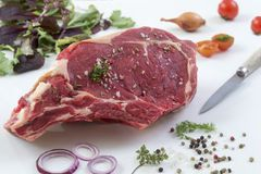 Raw T-bone Steak for grill or BBQ on cutting board with knife over on a white background, top view Stock Image