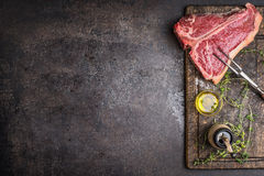 Raw T-bone Steak for grill or BBQ with meat fork and flavoring on aged cutting board and dark rustic metal background, top view Royalty Free Stock Photo