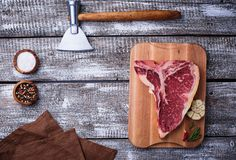 Raw T-bone steak with hatchet. Top view Royalty Free Stock Image