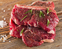 Raw T-Bone Steak with Seasoning and Rosemary on a wooden board. Royalty Free Stock Photography