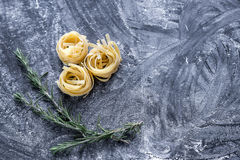 Raw tagliatelle nido on the flour-dusted black wooden background Stock Photography
