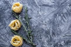 Raw tagliatelle nido on the flour-dusted black wooden background Royalty Free Stock Photography