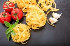 Raw tagliatelle pasta on black background. Raw tagliatelle on black background Royalty Free Stock Photography
