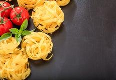 Raw tagliatelle pasta on black background. Raw tagliatelle on black background Stock Photos