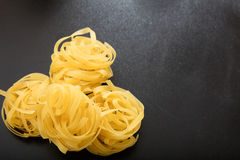 Raw tagliatelle pasta on black background. Raw tagliatelle nests on black background Stock Photo