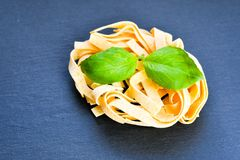 Raw pasta. Raw tagliatelle pasta with  fresh basil  and organic egg Royalty Free Stock Image