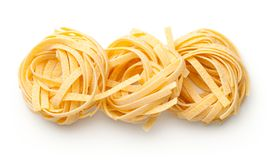 Raw Tagliatelle Pasta Nests Isolated On White Background. Top view royalty free stock images