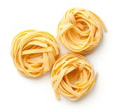 Raw Tagliatelle Pasta Nests Isolated On White Background. Top view stock images