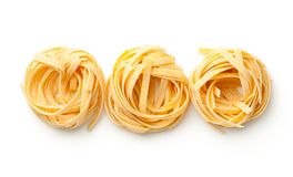 Raw Tagliatelle Pasta Nests Isolated On White Background. Top view stock photo