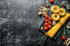 Raw tagliatelle and spaghetti with mushrooms, tomatoes and spices royalty free stock photo