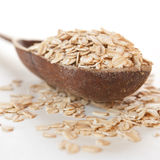Raw thick rolled oats. In a wooden spoon Stock Photo