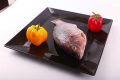 Raw Tilapia fish. On black plate Royalty Free Stock Photo