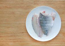 Raw tilapia fish fillet on white plate against wooden board background with copy space stock photo