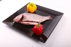 Raw Tilapia fish. On black plate Royalty Free Stock Images