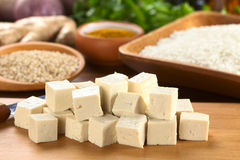 Raw Tofu Cut in Dices. On wooden board with rice and other raw ingredients in the back (Selective Focus, Focus on the front of the tofu Stock Photo