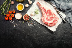 Raw tomahawk beef steak. With ingredients for grilling: seasoning, fresh rosemary and olive oil on paper over black background, top view stock image