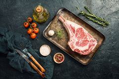 Raw tomahawk beef steak. With ingredients for grilling: seasoning, fresh rosemary and olive oil on black background, top view stock photo