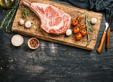 Raw tomahawk beef steak. With ingredients for grilling: seasoning, fresh rosemary and olive oil on cutting board over black background, top view Stock Photography