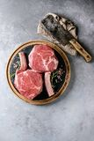 Raw tomahawk steak. Raw uncooked black angus beef tomahawk steaks on bones served with salt, pepper, vintage butcher cleaver on round wooden slate cutting board Royalty Free Stock Images