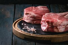 Raw tomahawk steak. Raw uncooked black angus beef tomahawk steaks on bones served with salt and pepper on round wooden slate cutting board over dark wooden plank Stock Images