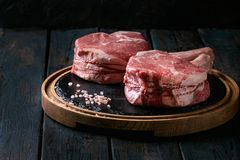 Raw tomahawk steak. Raw uncooked black angus beef tomahawk steaks on bones served with salt and pepper on round wooden slate cutting board over dark wooden plank Stock Photography