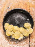 Raw Tortellini in black plate on wooden background with wheat flour Royalty Free Stock Photography