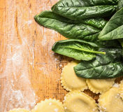 Raw Tortellini with  fresh spinach leaves on wooden background with wheat flour, top view Stock Photos