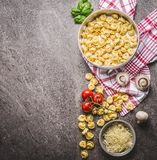 Raw tortellini pasta in bowl with ingredients, ready for cooking on rustic background , top view . Italian cuisine. Food concept Stock Photos