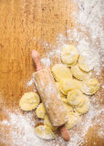 Raw Tortellini with Rolling pin on wooden background with wheat flour. Top view Stock Photo