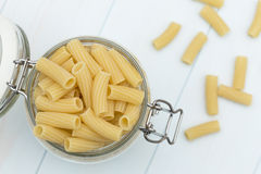 Raw tortiglioni pasta on a glass jar. On blue wood table Royalty Free Stock Photo