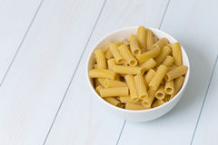 Raw tortiglioni pasta in a white bowl. On blue wood table Royalty Free Stock Photography