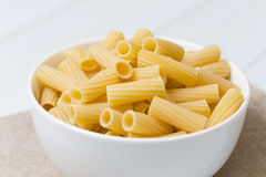 Raw tortiglioni pasta in a white bowl Stock Images