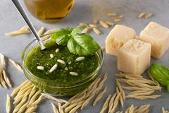 Raw trofie pasta and a glass bowl with pesto souace. Homemade green basil pesto sauce and fresh ingredients. Italian Cuisine. Top view with selective soft focus stock photos
