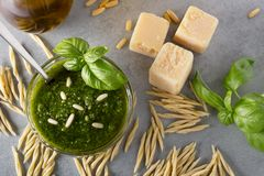 Raw trofie pasta and a glass bowl with pesto souace. Homemade green basil pesto sauce and fresh ingredients. Italian Cuisine. Top view with selective soft focus stock images