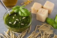Raw trofie pasta and a glass bowl with pesto souace. Homemade green basil pesto sauce and fresh ingredients. Italian Cuisine. Top view with selective soft focus stock photo