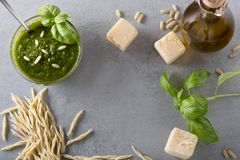 Raw trofie pasta and a glass bowl with pesto souace. Homemade green basil pesto sauce and fresh ingredients. Italian Cuisine. Top view with selective soft focus royalty free stock photo