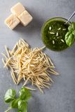 Raw trofie pasta and a glass bowl with pesto souace. Homemade green basil pesto sauce and fresh ingredients. Italian Cuisine. Top view with selective soft focus royalty free stock image
