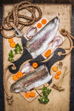 Raw trout fillet on cutting board with gut vegetables, top view. Healthy food and diet cooking. Concept Stock Image