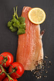 Raw trout fillet on slate. Raw trout fillet with slice lemon, wet tomato crushed peppercorn and fresh coriander on slate Stock Photography